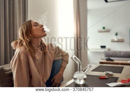 Young Caucasian Woman Exhaling The Smoke While Smoking Marijuana From A Bong Or Glass Water Pipe, Si