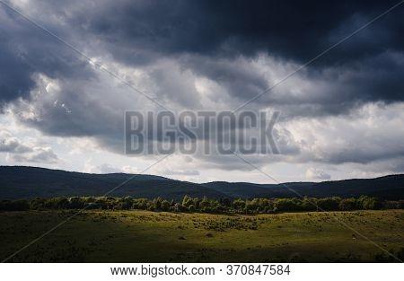 Dramatic Sky With Dark Rain Clouds And Sunshine Illuminating Green Slopes