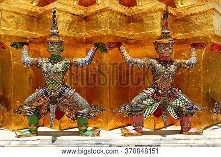 Two Giant Ramayana Statues Liftting Golden Pagoda At Wat Pra Kaew, Grand Palace, Bangkok, Thailand.