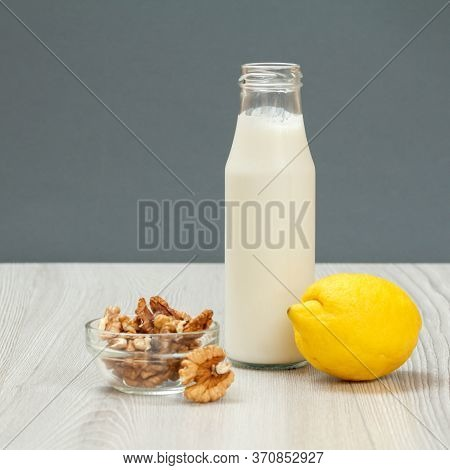 Health Remedy Relief Foods And Drink For Cold And Flu. Bottle Of Yogurt, A Lemon And Walnuts On Wood