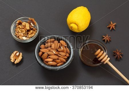 Health Remedy Relief Foods For Cold And Flu With Lemon, Honey And Walnuts On A Black Background. Top