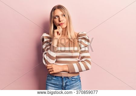 Young blonde woman wearing casual clothes thinking concentrated about doubt with finger on chin and looking up wondering