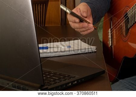 Taking Notes And Playing The Spanish Guitar At Home While Doing The Course Online From Home With The