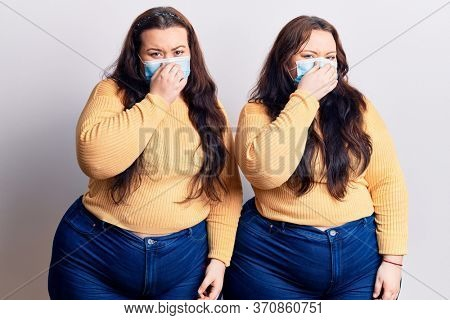 Young plus size twins wearing medical mask smelling something stinky and disgusting, intolerable smell, holding breath with fingers on nose. bad smell