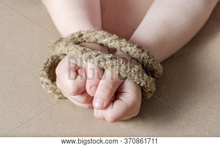 Child  Hands Tied With A Rope .concept Regarding Sexual Slavery .