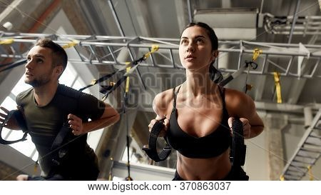 Athletic Young Woman Doing Fitness Trx Training Exercises At Industrial Gym. Push-up, Group Workout