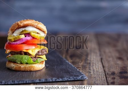 A Large, Juicy Double Cheeseburger Made With Two 100% Beef Patties, Slices Of Melted Cheese, Onions,