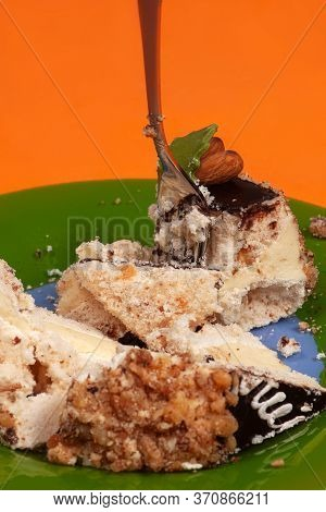 Close Up Green Plate With Broken Piece Of Cream Cake And Fork, Sticking Out There. Anti Diet Concept
