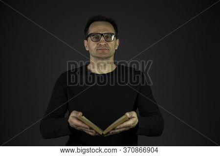 Smart Adult Intelligent Man In Casual Black Wear And Glasses Holding Old Open Book In Front Of Him A