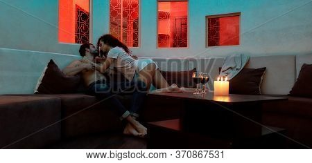 Young Sexy Man And Woman Are Kissing Before Having Sex On The Couch In The Evening. Caucasian Couple