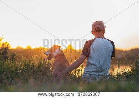 Man Hugs His Dog In Sunset By The Lake. Pets And Human Friendship, Taking Care, Spending Time Togeth