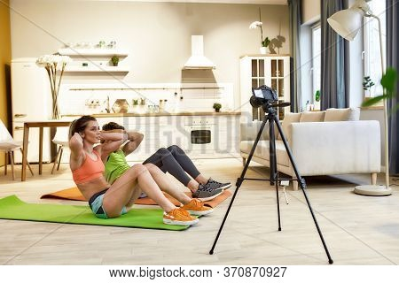 Young Couple In Sportswear Recording Video Blog Or Vlog About Healthy Lifestyle On Camera While Exer