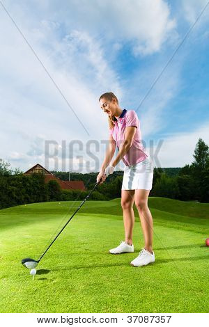 Young female golf player on course doing golf swing, she presumably does exercise