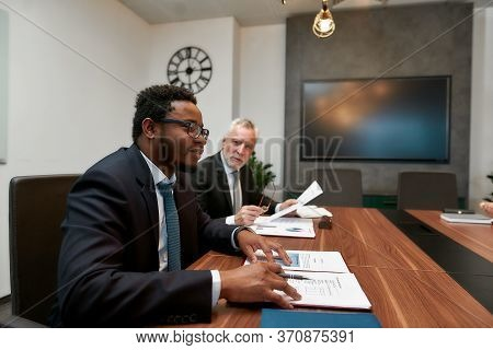 Caucasian And African Businessmen Discussing Something While Working Together In The Modern Office.