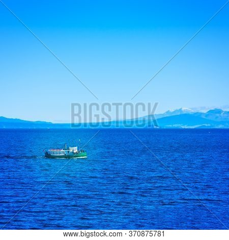 Tourist Steamboat In The Deep Blur Waters Of Taupo Lake With Ruapehu Mountains In The Background On