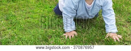 Unrecognizable One-year-old Child In A Blue Jacket And Jeans Crawls On The Green Grass In The Backya