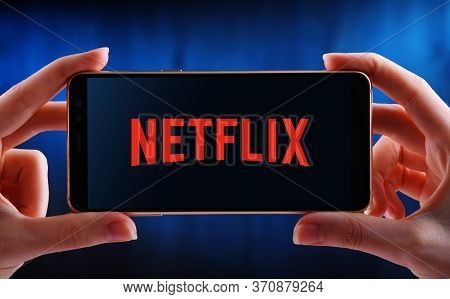 Hands Holding Smartphone Displaying Logo Of Netflix