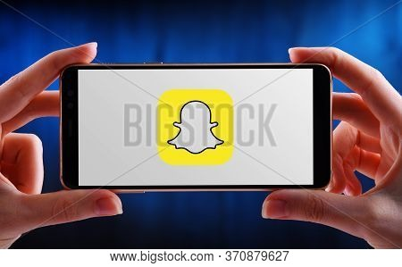 Poznan, Pol - May 21, 2020: Hands Holding Smartphone Displaying Logo Of Snapchat, A Multimedia Messa
