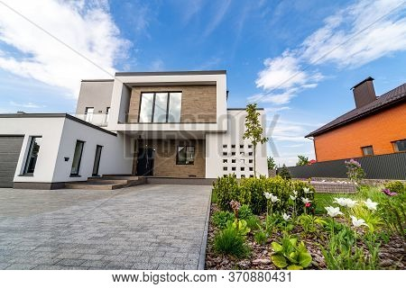 Luxury House With Garage. Blue Sky Above. Nobody In The Yard. Modern Architecture. Cozy And Modern H