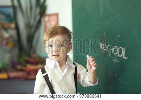 Boy With Chalk Over Green Chalkboard. Preschool Or School Concept
