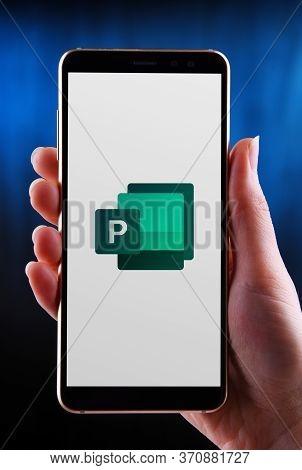 Poznan, Pol - May 21, 2020: Hands Holding Smartphone Displaying Logo Of Microsoft Publisher, A Deskt