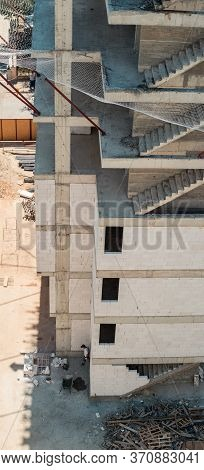 High Angle View Of A Building Under Construction With Unfinished Concrete Staircases And Constructio