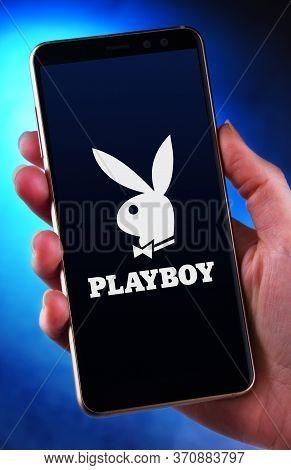 Hands Holding Smartphone Displaying Logo Of Playboy