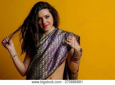 The Young Dark-haired Woman In A Bright Indian Sari Smiling Holding Arm Hair Strand. Indian Style.