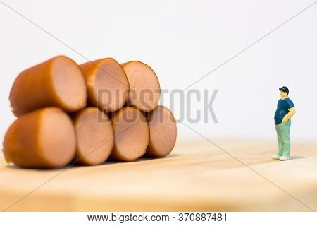 Miniature People : Close Up Fat Man Standing And Looking At Sausages Isolated On White Background (f