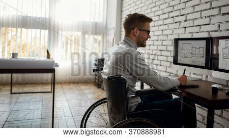 Young Smiling Male Engineer Or Architect In A Wheelchair Using Stylus Pen And Digital Tablet While S