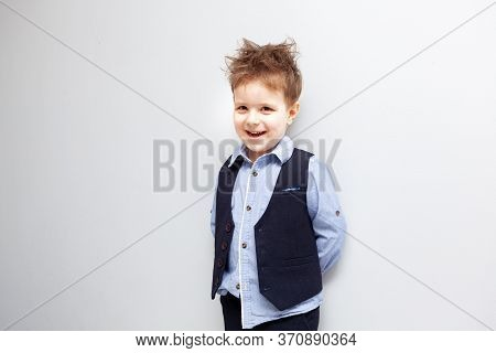 A Boy With Disheveled Hair In A Shirt, Vest And Trousers Stands Against A White Background. The Chil