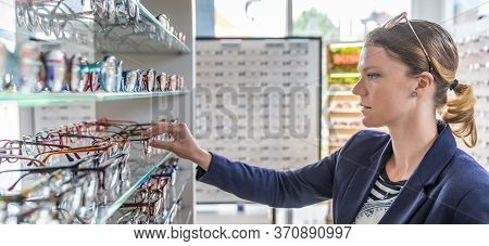 Choosing Glasses In Optics Store By Young Woman. Copy Space