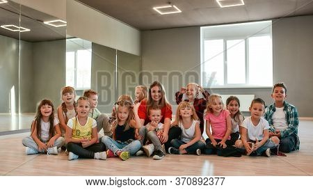 Making A Photo. Group Of Positive Little Boys And Girls In Fashionable Clothes Posing With Their You
