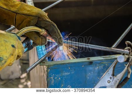 Industrial Worker Labourer Welding In Gloves Steel Structure, A Metal Product Is Welded With A Weldi