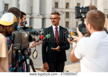 Horizontal Shot Of Serious Politician Looking At Reporters And Giving Interview To Them. People Maki