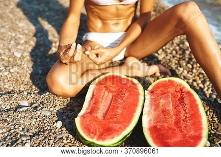 Woman In White Bikini Sitts On Pebble Beach With Two Halves Of Huge Ripe Watermelon
