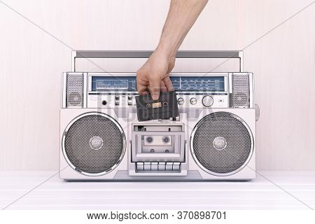 Hand Inserting A Tape Of Music Into The Deck Of A Vintage 80s Radio Cassette. Play Music Concept.