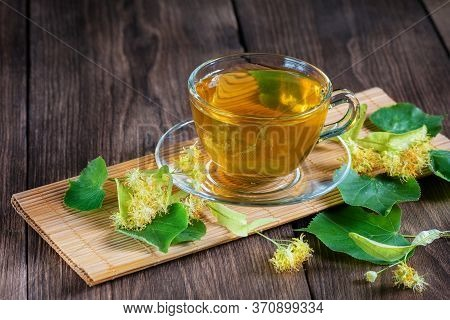 A Cup Of Lime Tea, Standing On A Wooden Table, Surrounded By Fragrant Linden Flowers, In The Rays Of