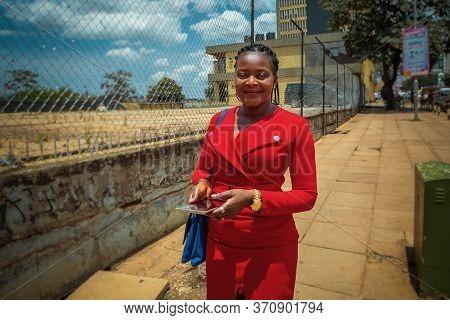 Kampala,uganda - April 13,2017:entebbe Road A Beautiful Business Woman In A Stylish Red Dress Was On