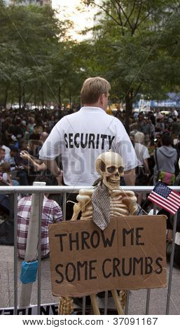 NEW YORK - SEPT 17: A security guard behind a sign that reads 'Throw Me Some Crumbs' in Zuccotti Park on the 1yr anniversary of the Occupy Wall St protests on September 17, 2012 in New York City, NY.