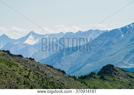 Beautiful Aerial View To Green Forest Mountainside With Crags And Great Snowy Mountains. Awesome Alp