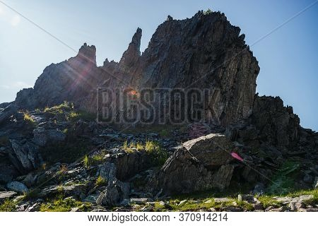 Vivid Solar Flare And Sunny Beams On Silhouette Of Big Sharp Rock. Great Pointy Stone Among Greenery