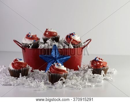 Mini Chocolate Cupcakes With Red And White Swirled Frosting And Star Sprinkles With Some In A Red Bu