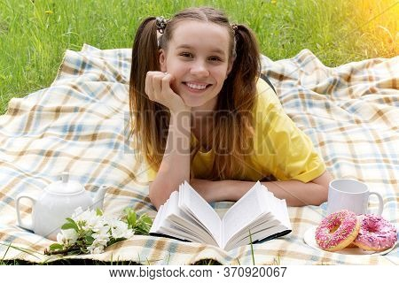 A Smiling Girl In The Morning Lies On A Plaid In The Countryside And Reads A Book. Nearby Is A Mug W