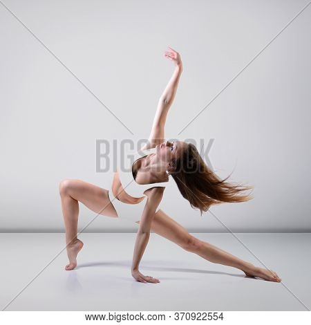Dance. Young beautiful graceful woman with perfect slim sporty body dancing and jumping at studio over gray background. Female beautiful contemporary dance. Ease of movement, youth, grace