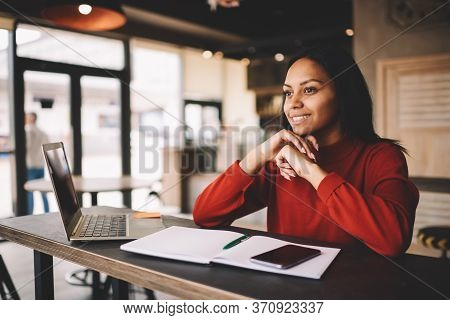 Happy Cheerful Female Student Sitting In Coworking Space With Textbook For Education