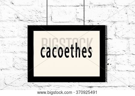 Black Wooden Frame With Inscription Cacoethes Hanging On White Brick Wall