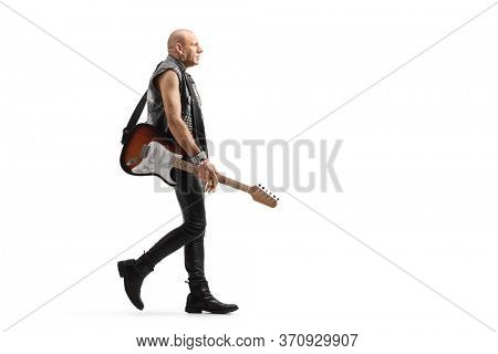 Full length profile shot of a punk rocker musician with a guitar walking isolated on white background