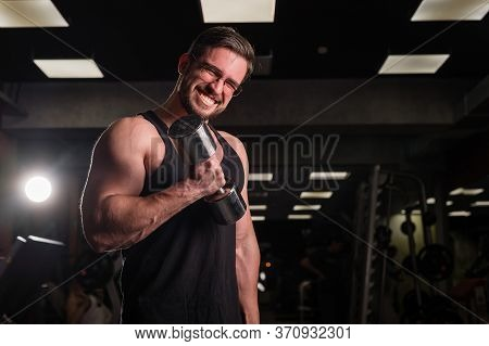 A Man With An Effort Does An Exercise For Biceps And Triceps With A Dumbbell. Embossed Bodybuilder S