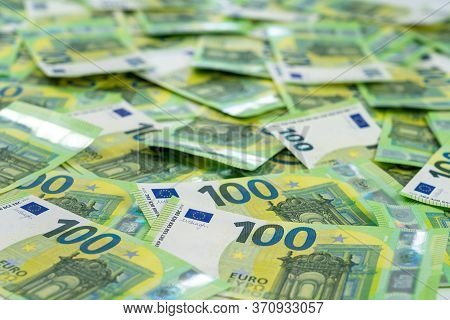 Banknotes Of 100 Hundred Euros Are Scattered In A Chaotic Manner. European Currenc. Side View, Close